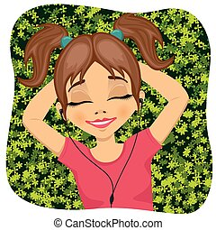 Relaxed little girl lying on grass listening to music outdoors with eyes closed