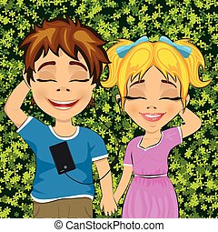 Little teenage boy and girl lying on grass listening to music outdoors with eyes closed