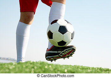 Playing soccer - Horizontal image of soccer ball being...