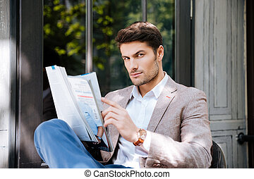 Man with magazine sitting in outdoor cafe - Attractive young...