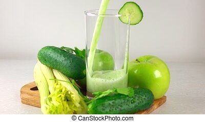 Pouring green smoothy in a glass. Apple, cucumber and...