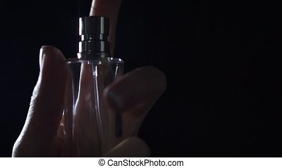 Beautiful woman hand sprays perfume at the camera, slow...