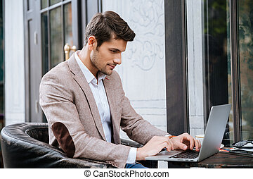 Man sitting and using laptop in outdoor cafe - Concentrated...