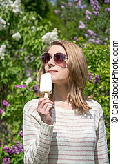 Girl eating ice cream on a lilac background