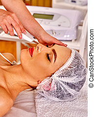 Woman receiving electric facial peeling massage - Woman...