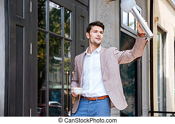 Young handsome businessman greeting someone at coffee shop...