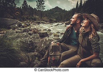 Cheerful couple hikers sitting near wild mountain river.