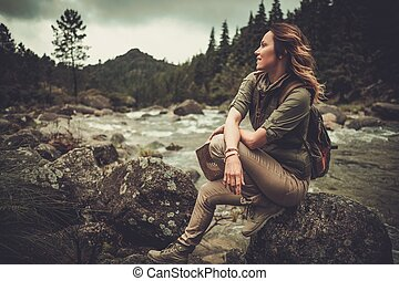 Beautiful woman hiker sitting on the stone near wild...