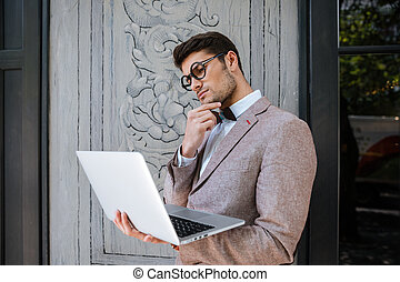 Man in funny round glasses thinking and using laptop -...