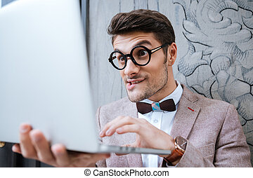 Nerd man holding laptop and making funny face - Nerd...