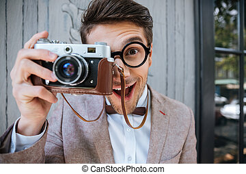 Happy stylish nerd with camera outdoors - Happy funny...