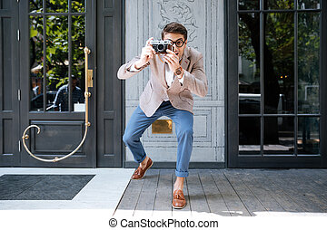 Cheerful funny photographer in round glasses taking pictures on street