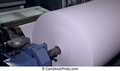 A wide paper roll is rotated on the machine for further cuts...