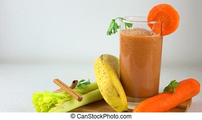 Orange smoothy in a glass. Banana, carrot, parsley and...