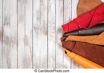 Brightly colored leather in rolls on white wooden...