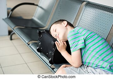 Tired child boy sleeping at the airport - canceled flight
