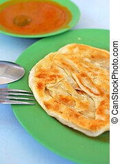 Indian traditional roti prata cuisine with curry side dish....