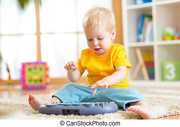 Happy kid boy playing piano toy in nursery room
