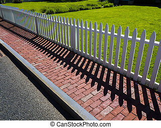 White picket fence separating front yard from brick sidewalk