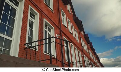 Clouds floating above row of red brick townhouses clip