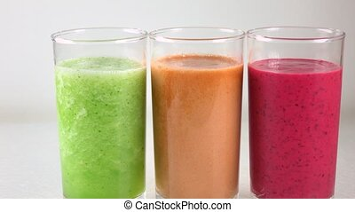 Three glasses of multicolored vegetable smoothies. 4K dolly...
