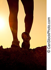 silhouette of fitness girl legs running at sunset