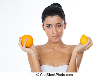 girl holding citrus - woman with fruits and grimace