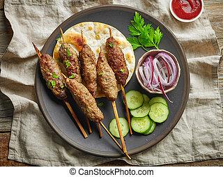 grilled minced meat skewers kebabs on dark plate, top view
