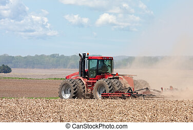 Farm Tractor - Farm tractor plowing the field before...
