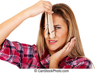 Young woman pinching her nose with a huge clothespin.