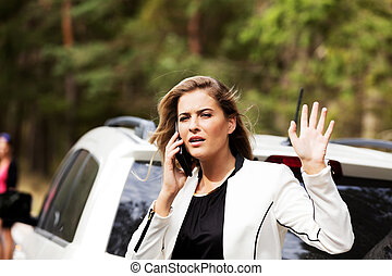 Woman with broken car talking through a phone and waving to...