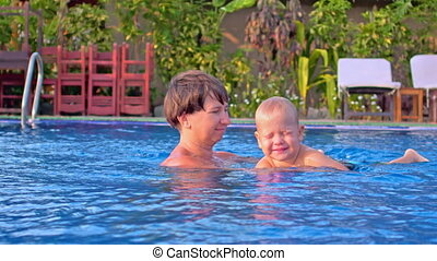 toddler boy tries to swim in pool