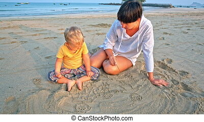 Baby and mother draw in sand on beach