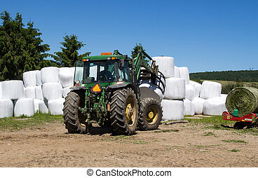 agriculture machinery picking up hay roll