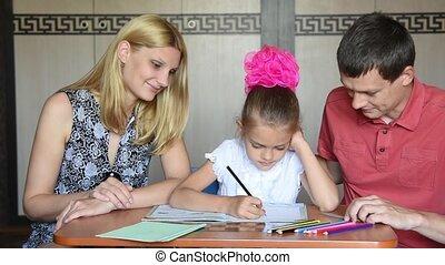 Schoolgirl doing homework with parents
