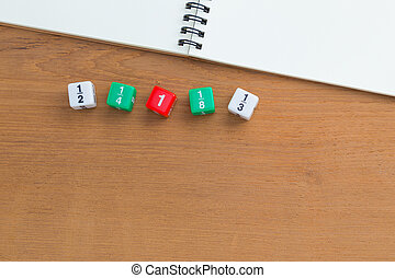 Color fraction dices, blank white notebook on wooden desk,...