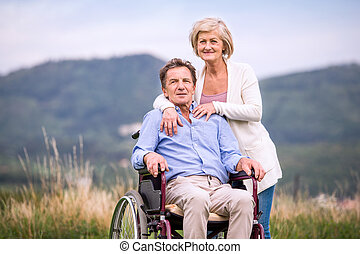 Senior woman pushing man in wheelchair, green autumn nature...