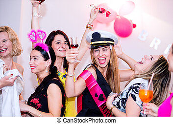 Cheerful bride and bridesmaids celebrating hen party with...