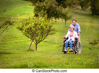 Senior man pushing woman in wheelchair, green autumn nature...