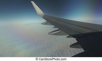 Passenger aircraft flying high above the clouds. Porthole...