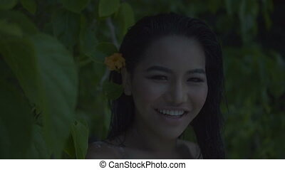 Happy woman with flower in her hair - Asian beautiful happy...