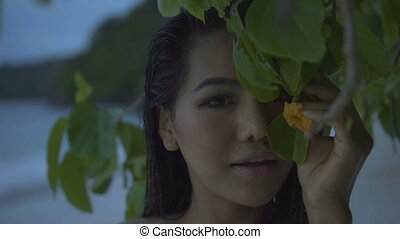 Woman smelling flower on the beach - Closeup of asian...