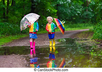 Kids playing in the rain - Little boy and girl play in rainy...