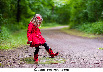 Little girl walking in the rain - Little girl playing in...