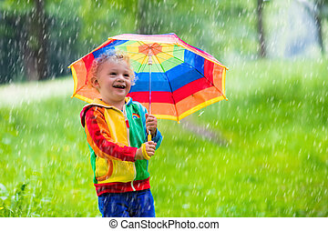 Child playing in the rain - Little boy playing in rainy...