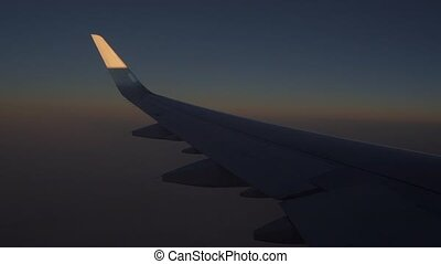 Passenger aircraft flying high at late sunset. View from...