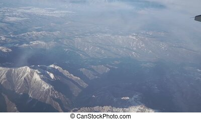 Snow covered mountains in sunny weather, aerial view clip