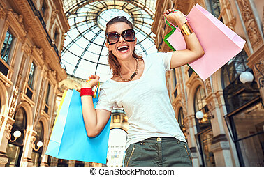 Woman with shopping bags in Galleria Vittorio Emanuele...