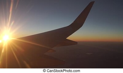 Passenger aircraft flying high at beautiful sunset. View...