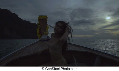 Woman on boat with wind in hair - Asian beautiful sensual...